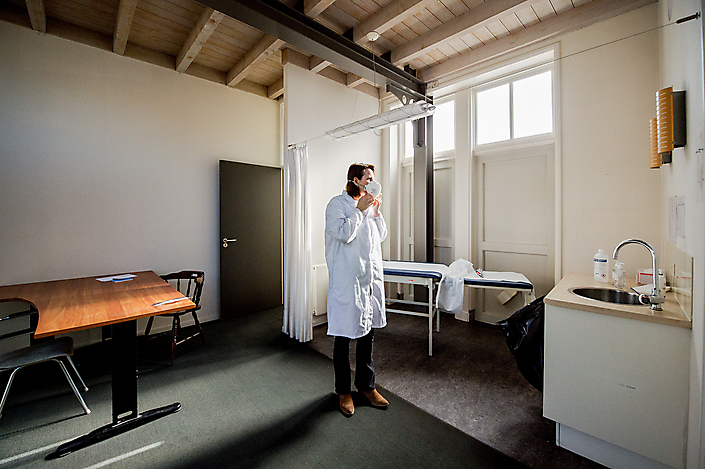 Huisarts trekt beschermende kleding aan in isolatiepraktijk voor coronapatienten, Boxtel