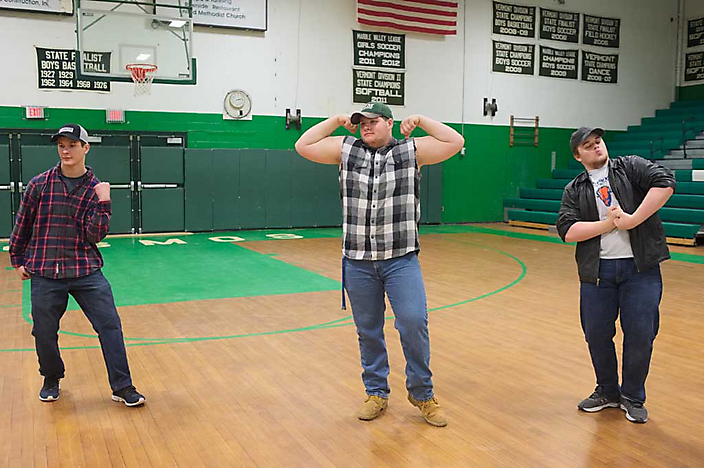 Dance partners Logan, Bradley, and Ethan (from left) learn in 2018 to express toughness for the 62nd Apple Blossom Cotillion in the gymnasium of the Riverside School.