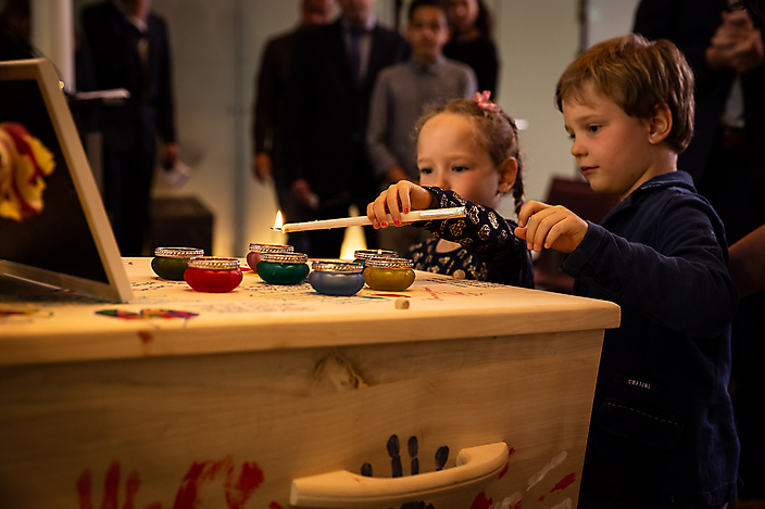 Kinderen steken kaarsjes aan op de kist.