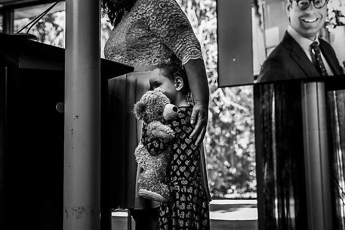 Meisje kruipt stevig tegen haar moeder met de knuffelbeer in haar armen.
